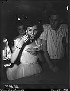 Woman eating spaghetti and man wearing ribbon 'Souvenir of Port Douglas Electricity 13th April 1957', Port Douglas, Queensland