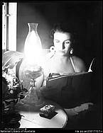 Woman reading magazine by light of kerosene lamp, Port Douglas, Queensland, April 1957. This is the celebration of the first mains electricity in Port! Frank Hurley, photographer