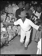 Aboriginal man dancing surrounded by small crowd, Port Douglas, Queensland, April 1957