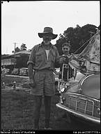 Man beside car holding kerosene lamp, Port Douglas, Queensland, April 1957